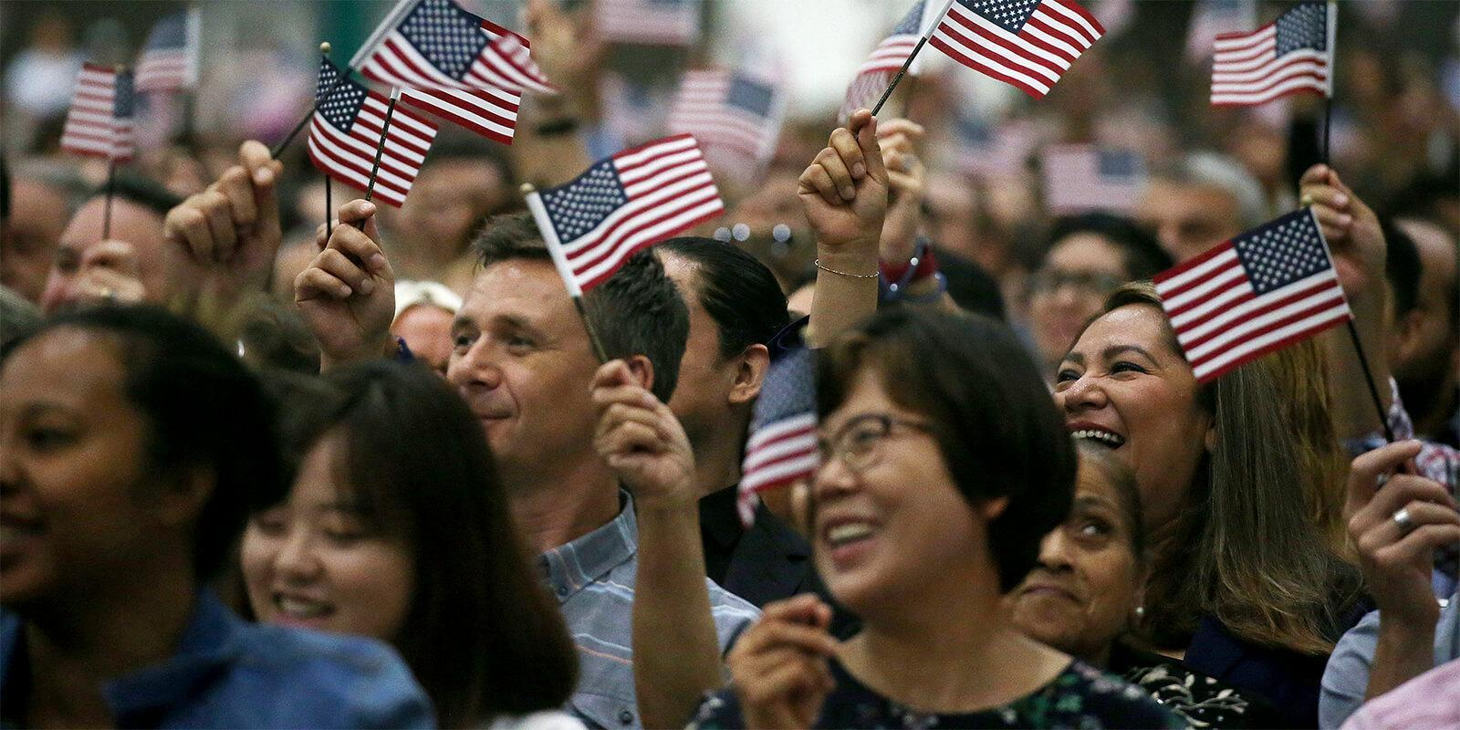 Diverse crowd of people waving small American flags